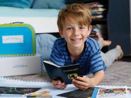 a young boy aged 6 years old opening a new gift pack with books, accessories and items surrounding him