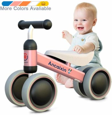 This is an image of a pink balance bike besides a baby.