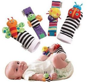 a smiling baby wearing blige baby socks rattles