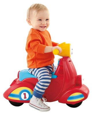This is an image of a baby riding a red scooter by Fisher Price.