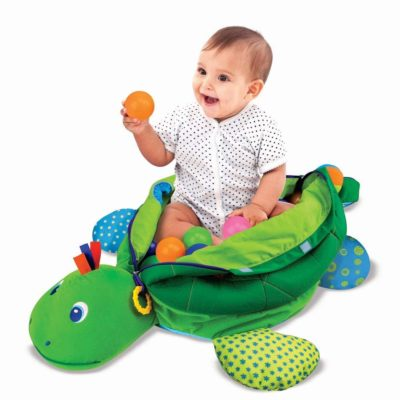 This is an image of a little kid using a green turtle ball pit by Melissa and Doug.