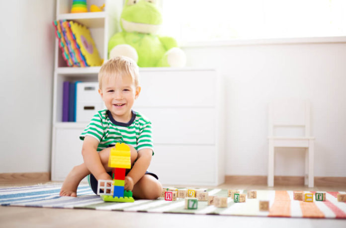 happy two years old child sitting on the floor with toys. Pretty little boy palying with wooden cubes at home