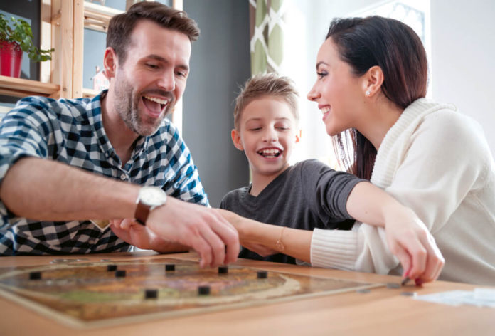 7 year old boy with parents playing board game at home, happiness concept