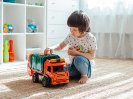 three year old girl playing with a toy car at home. Girl playing game. The child is 3 years