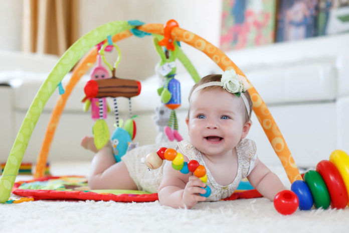 baby playing. little baby playing with toys at home. happy child girl sitting on floor in nursery. 6 months baby girl