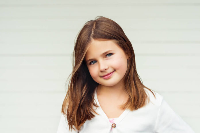 Outdoor portrait of cute little 8 year old girl with brown hair, wearing white jacket, standing against white background