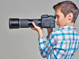 Teen boy with photo camera photographing. Boy with camera taking pictures. Profile portrait.
