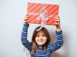 6 year old girl holding up a wrapped gift