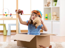 4 year old girl child pilot flying a cardboard box in kid rooms surrounded by toys
