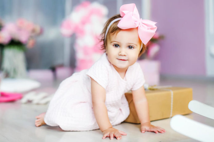 Baby in a dress, in a pink komnata. Birthday, one year old girl