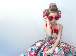 6 year old girl wearing sun glasses, pearl neckless and a pretty dress,