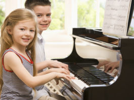 2 young kids playing piano and looking into the camera smiling