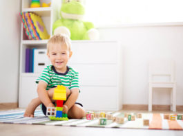 happy 18 month old child sitting on the floor with toys. Pretty little boy palying with wooden cubes at home