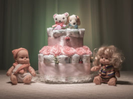 Newborn gift concept. Cake of diapers. Wrapped diapers as cake with flowers. Cake of wrapped clean diaper on table with baby doll decorated. Selective focus.