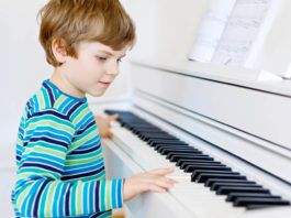 Beautiful little kid boy playing piano in living room or music school. Preschool child having fun with learning to play music instrument. Education, skills concept.