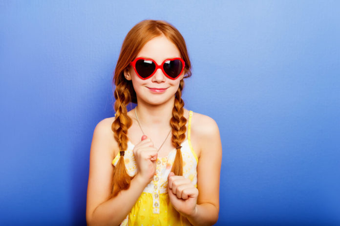 Studio shot of young preteen 9 year old redhead girl wearing heart shape sunglasses, standing against blue purple background