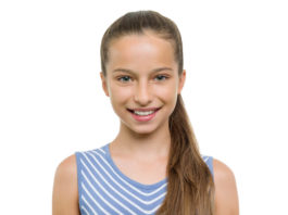 Portrait of beautiful girl of 11 years old. Child with perfect white smile, isolated on white background.