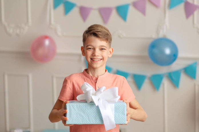 Happy Birthday Portrait of a happy cute boy of 9 years old in a festive decor with confetti and gifts.