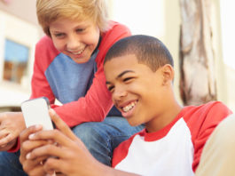 Two Teenage Boys aged 13 years old Reading Text On Mobile Phone