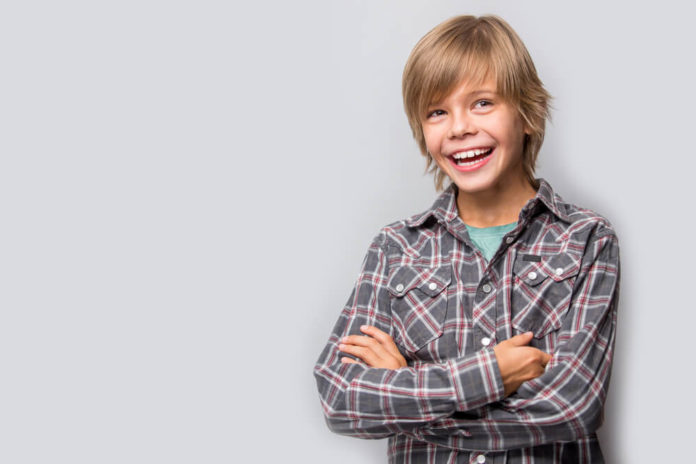 Photo of adorable 10 year old young happy boy wearing shirt looking at camera over grey background