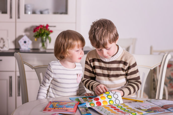 this is an image of toddlers doing a sticker book