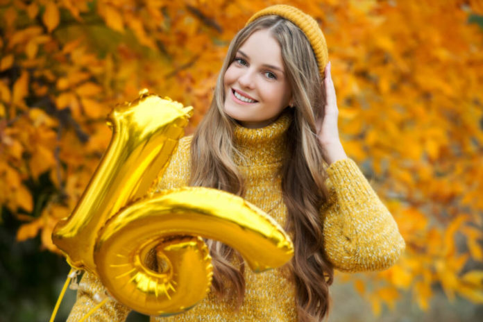 Beautiful girl walking outdoors in autumn. Smiling girl with gold balloons. Birthday 16 years old.