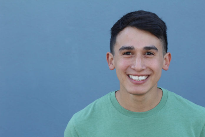 Close up portrait of a 16 year old boy teenager man looking at camera with a joyful smiling expression, against a blue background. Teenager being confident and smart.