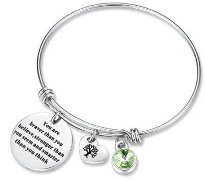 This is an image of girl's braver than you believe birthday gift bracelet with a quote and a heart. Silver color